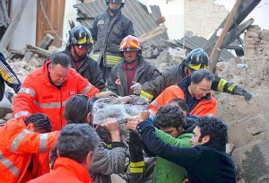 Italian rescue teams retrieve a person from a building which collapsed following an earthquake